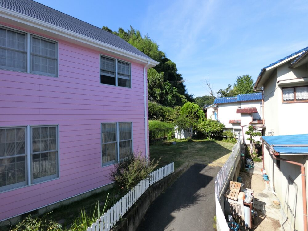 外壁塗装後はピカピカで青空と緑の木々にかわいらしいピンクが映えますね
